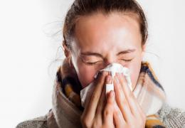 woman with fall scarf on sneezing into a tissue