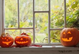 autumn leaves through window of home with carved pumpkins