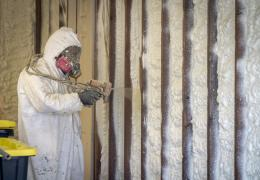 worker applying spray-foam insulation to a wall