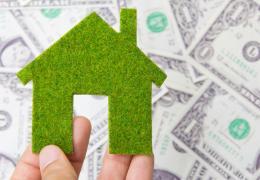 green home model over dollar bills, energy audit savings concept