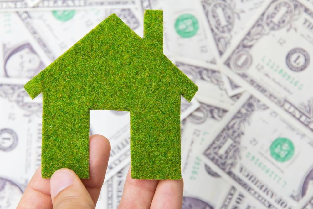 green home model over dollar bills, energy audit savings concept